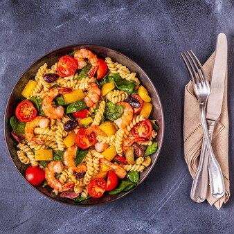 Fusili-nudelsalat mit garnelen, tomaten, paprika, spinat, oliven
