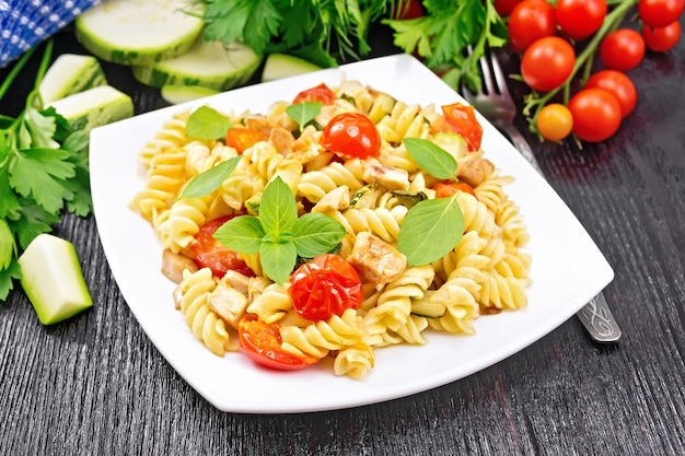 Fusilli mit hühnchen, zucchini und tomaten in einem weißen teller, serviette, gabel, basilikum und petersilie auf schwarzem holzbretthintergrund