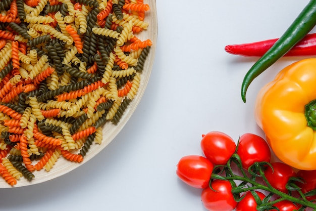 Fusilli-nudeln in einem teller mit tomaten, paprika flach auf einem weißen tisch liegen
