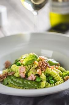 Fusilli-nudeln mit grünem erbsenschinken und walnüssen. italienische oder mediterrane küche.