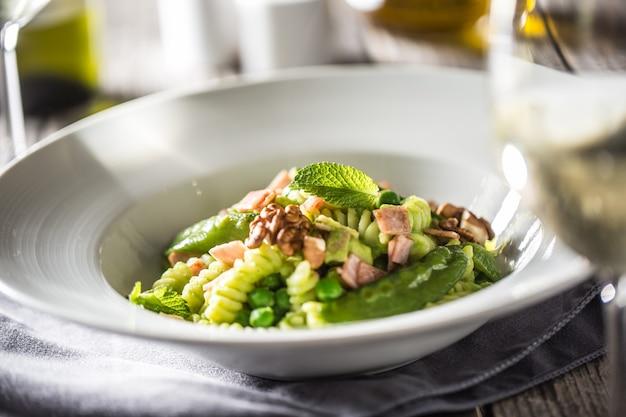 Fusilli-nudeln mit grünen erbsen-schinken-walnüssen mit weißwein. italienische oder mediterrane küche.