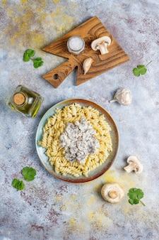 Fusilli-nudeln mit pilzen und hühnchen, draufsicht