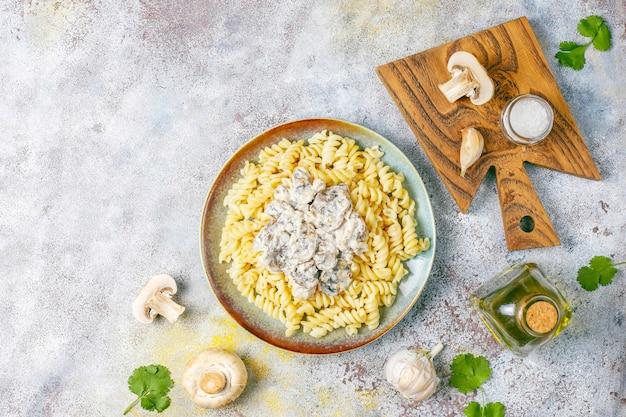 Fusilli-nudeln mit pilzen und hühnchen