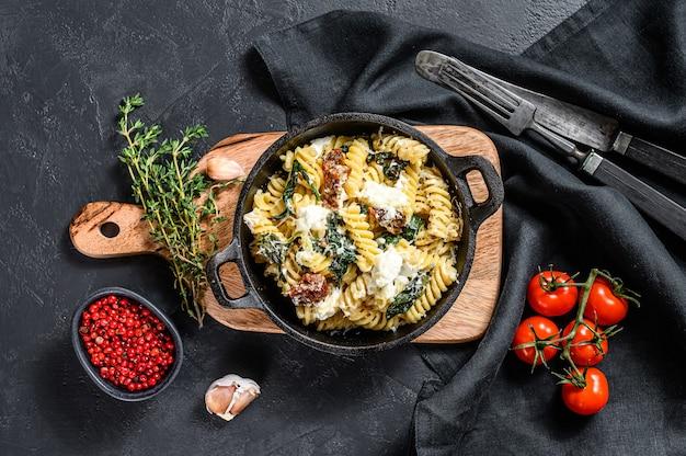 Fusilli-nudeln mit spinat, getrockneten tomaten und ricotta-käse ua in einer pfanne. schwarzer hintergrund. draufsicht.
