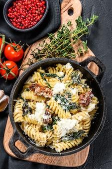 Fusilli-nudeln mit spinat, getrockneten tomaten und ricotta-käse ua in einer pfanne. schwarzer hintergrund. draufsicht