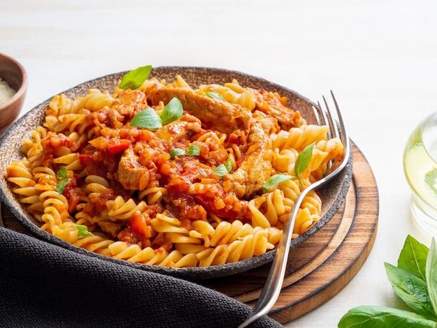 Fusilli-nudeln mit tomatensauce, hähnchenfilet mit basilikumblättern