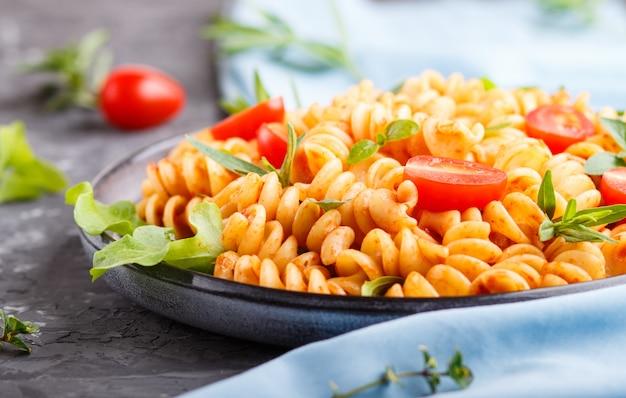 Fusilli nudeln mit tomatensauce, kirschtomaten, salat und kräutern