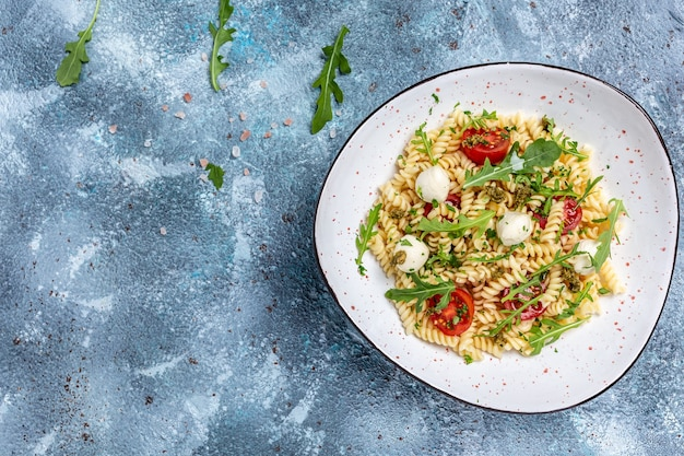 Fusilli pasta caprese-salat mit tomate, mozzarella-gemüsepaste auf blauem hintergrund, frisch, salat, banner, menü, rezept. gesundes essen,