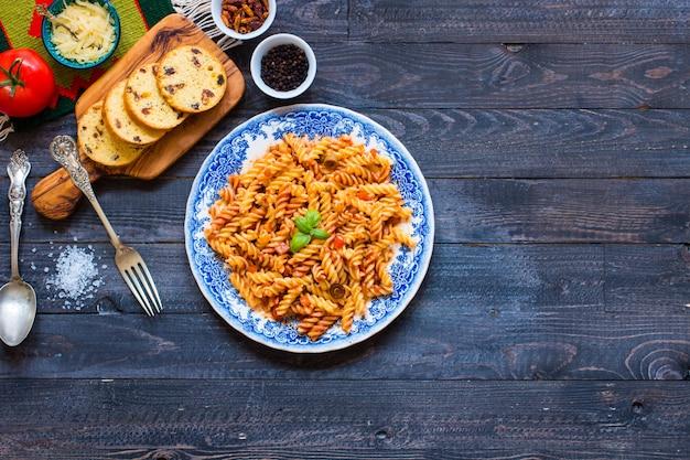 Fusilli-teigwaren mit tomatensauce, tomaten, zwiebel, knoblauch, getrocknetem paprika, oliven, pfeffer und olivenöl auf einem holztisch