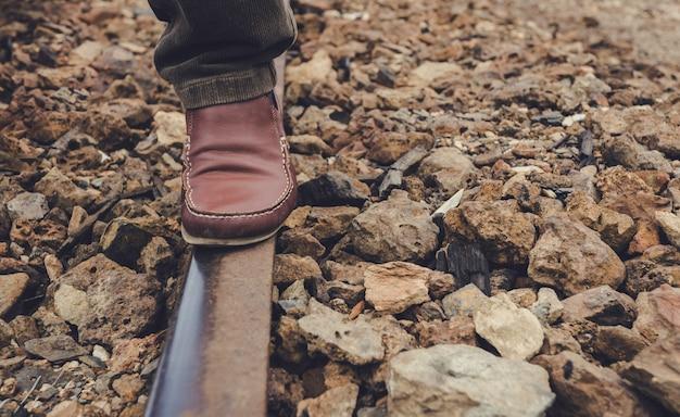 Fuß auf der schiene der bahnstrecke, auf dem steinboden im alten bahnhof von zaranda