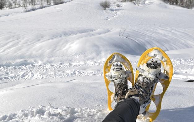 Fuß der frau mit schneeschuhen im schnee