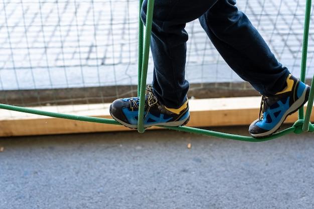 Fuß des kindes tut balancen auf hölzernen brettern in einem städtischen abenteuerpark.