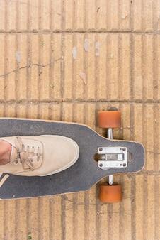 Fuß in turnschuhen auf longboard stehen
