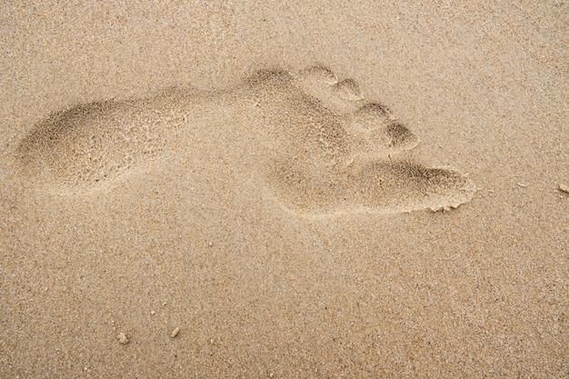 Fußabdruck auf dem strandsandhintergrund.