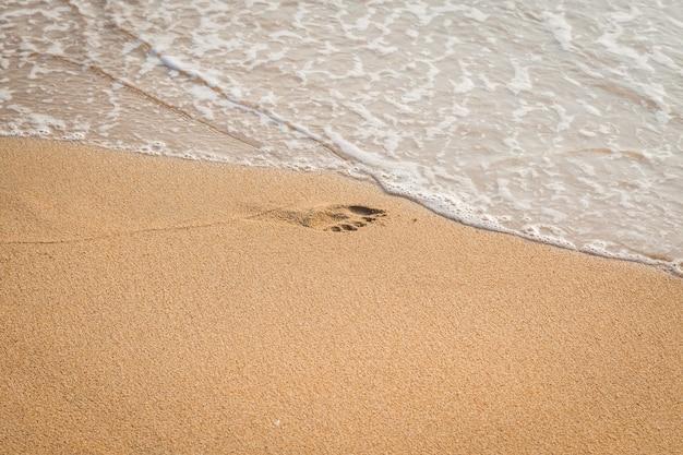 Fußabdruck des kindes auf dem strandhintergrund