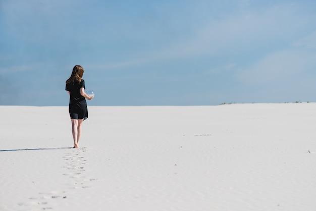 Fußabdrücke der frau, die mit aquarium in der wüste geht