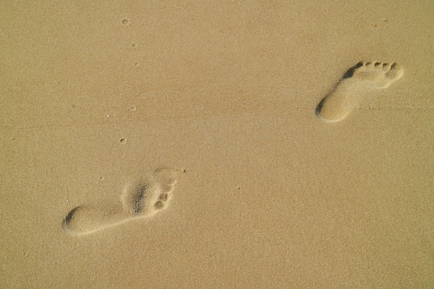 Fußabdrücke einer frau am sandstrand