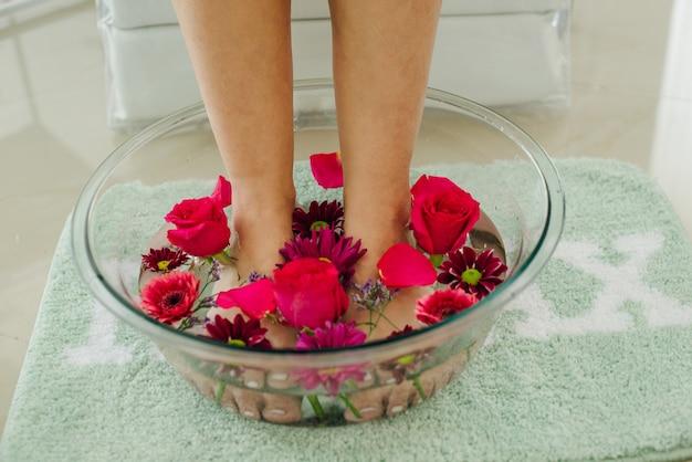 Fußbad in schüssel mit kalk und tropischen blumen, spa-pediküre, ansicht von oben.