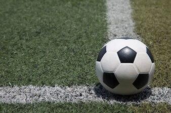 Fußball auf der weißen Linie auf grünem Fußballplatz-Grashintergrund
