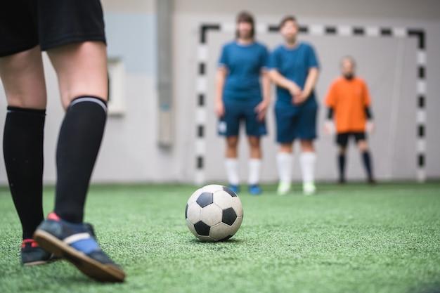 Fußball auf grünem fußballfeld mit beinen der jungen sportlerin, die ihn während des spiels zur gegnerischen mannschaft treten wird