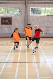 Fußball. drei kinder in sportbekleidung spielen drinnen fußball im fitnessstudio