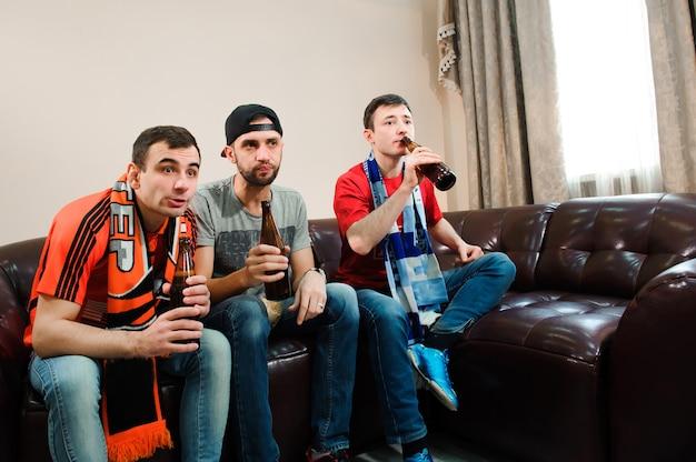 Fußball fans. männer trinken bier, essen pommes und wurzeln für fußball.