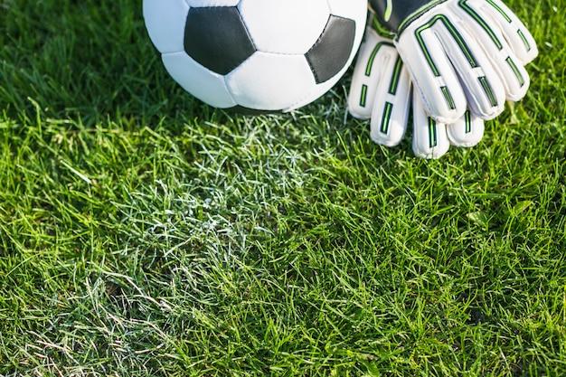Fußball im gras mit handschuhen