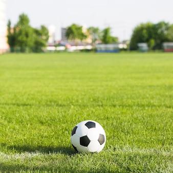 Fußball im gras mit unscharfem hintergrund