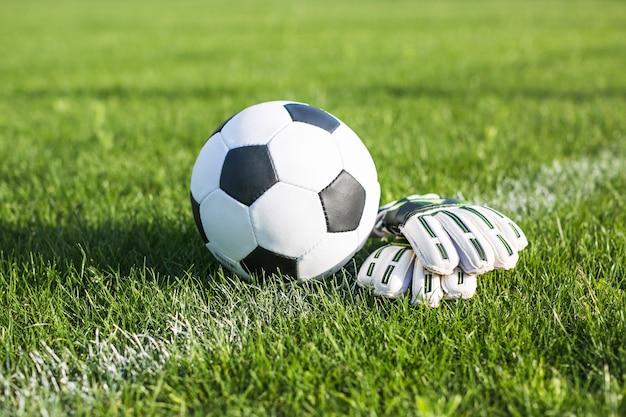 Fußball im gras neben handschuhen