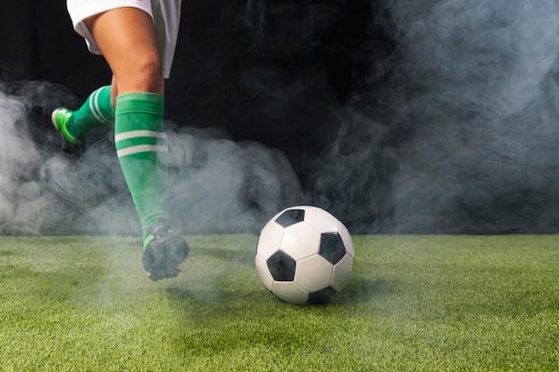Fußball in der sportkleidung, die mit ball spielt