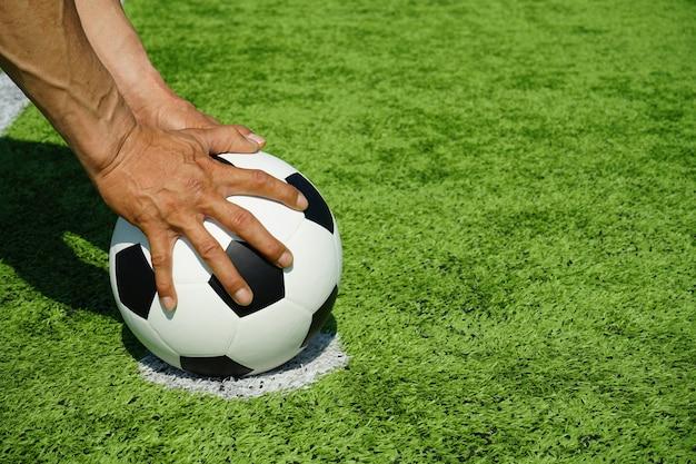 Fußball mit den händen und grünem gras