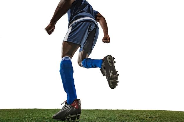 Fußball- oder fußballspieler auf weißer wand mit gras. überwindung. weiter winkel.