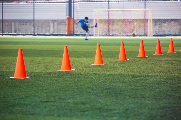 Fußball-taktik-kegel auf rasenfläche mit für trainingshintergrund training von kindern im fußball