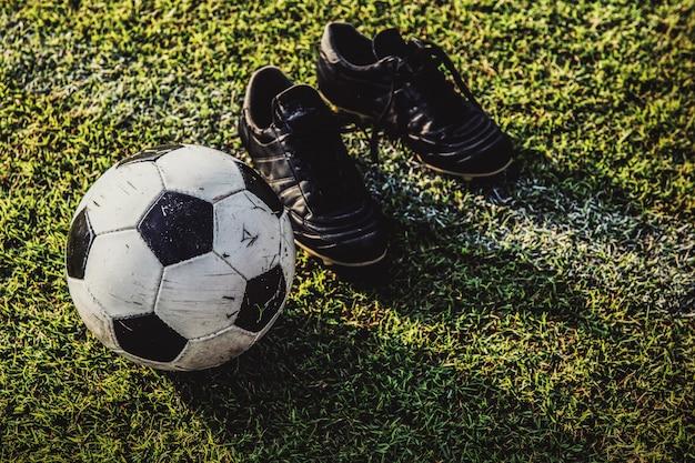 Fußball und stiefel auf grünem gras