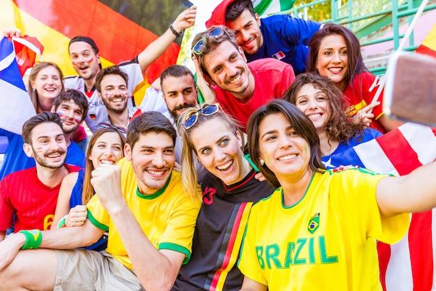 Fußballanhänger, der ein selfie am stadion nimmt