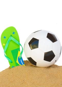 Fußballball im sand mit flipflop in den brasilianischen farben lokalisiert auf weißem hintergrundrand