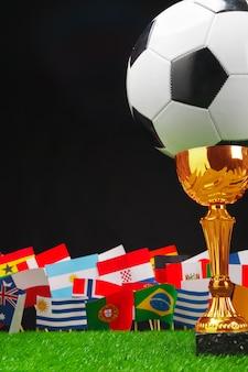Fußballcup mit fußballkugel auf gras