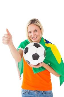 Fußballfan, der ball hält und brasilien-flagge trägt