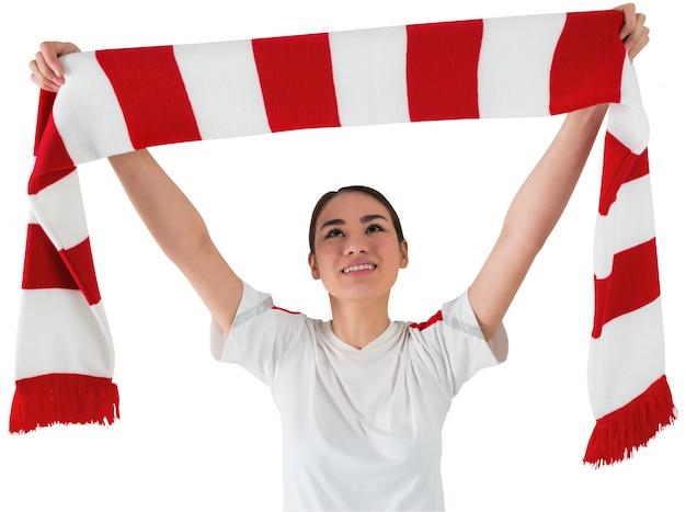 Fußballfan, der roten und weißen schal wellenartig bewegt