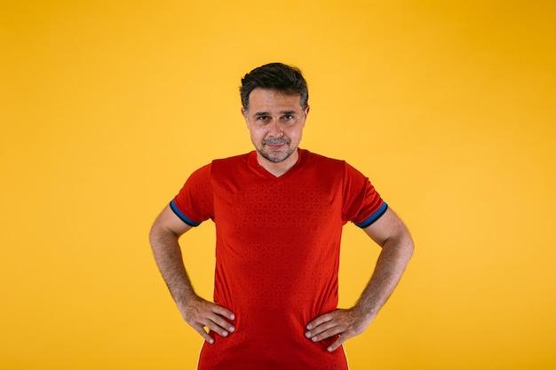 Fußballfan im roten hemd, posiert mit armen an der taille