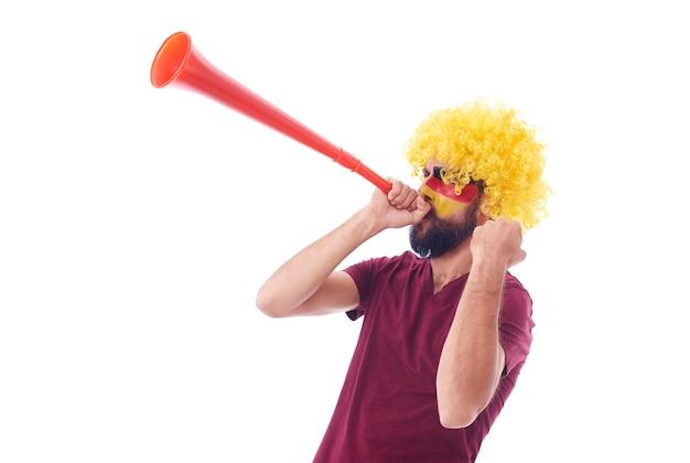 Fußballfan mit perücke und vuvuzela feiert