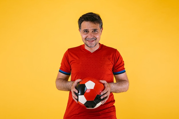Fußballfan mit rotem trikot und ball in den händen
