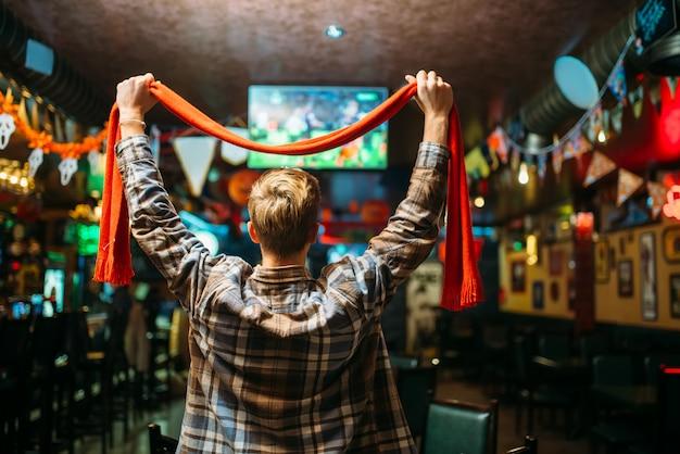 Fußballfan mit schal hebt die hände und beobachtet das spiel der lieblingsmannschaft in der sportbar, rückansicht. fernsehübertragung des spiels in der kneipe