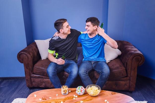 Fußballfans auf dem couchumarmen