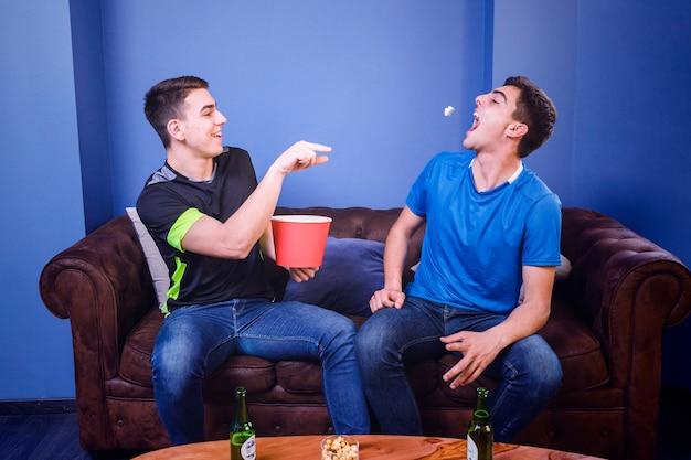 Fußballfans auf der couch mit popcorn