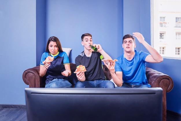 Fußballfans auf der couch vor dem fernseher