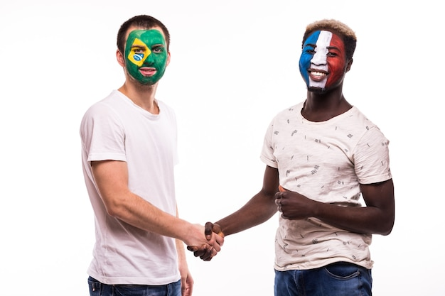 Fußballfans der brasilianischen und französischen nationalmannschaften mit gemaltem gesicht schütteln hände über weißem hintergrund