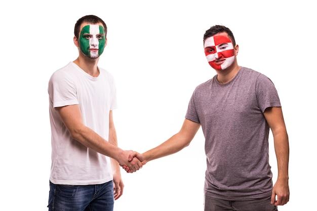 Fußballfans der nationalmannschaften von nigeria und kroatien mit bemaltem gesicht geben sich die hand