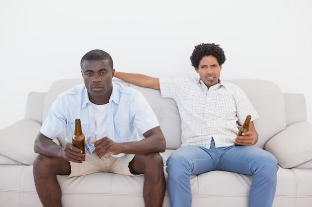 Fußballfans, die auf trinkendem bier der couch sitzen