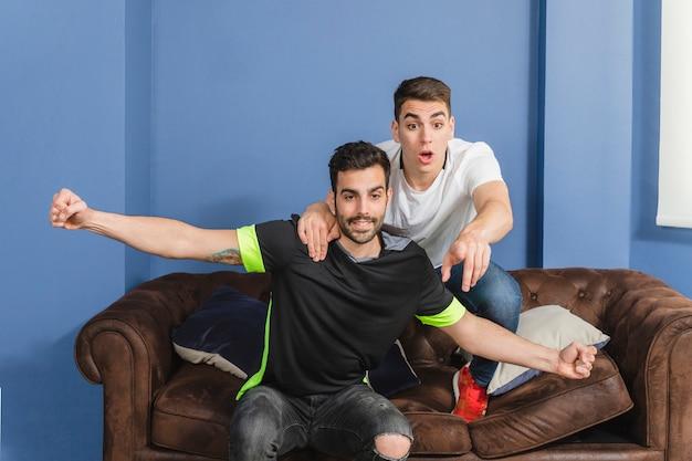 Fußballfans, die im wohnzimmer feiern
